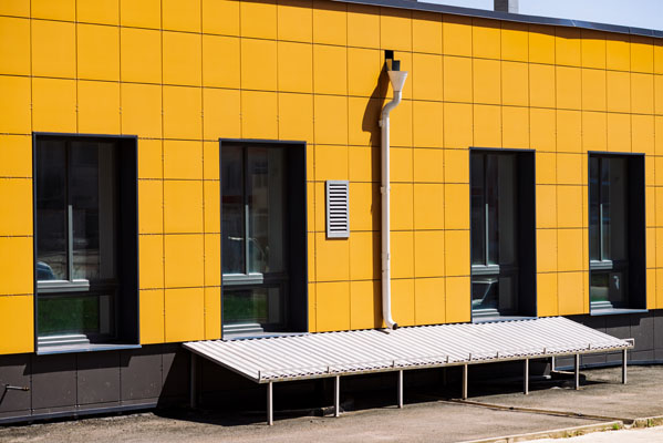 Facade of store building with big windows close-up. Industrial building with drain and basement. Wall restored by modern yellow tiles. Bright shop. Vivid architecture background with copy space.